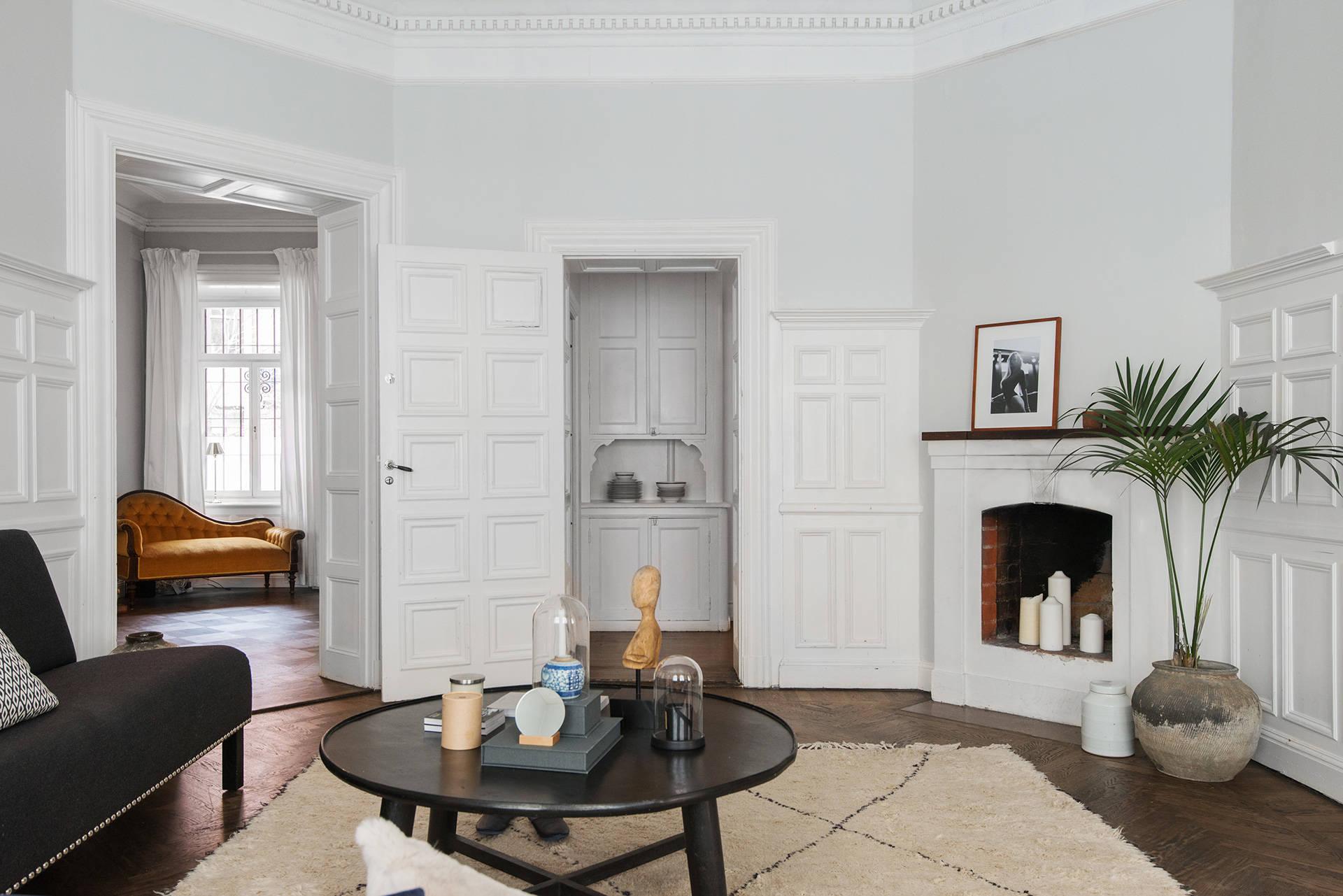 гостиная белые стены паркет молдинги стеновые панели камин ковер столик