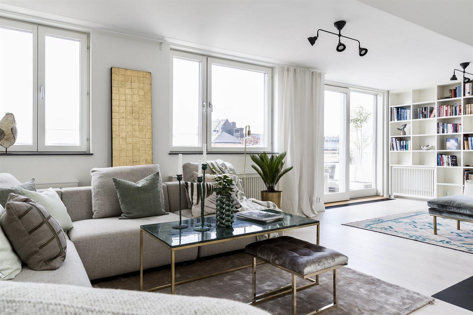 гостиная серый диван столик ковер светлая половая доска выход на балкон книжный стеллаж шкаф