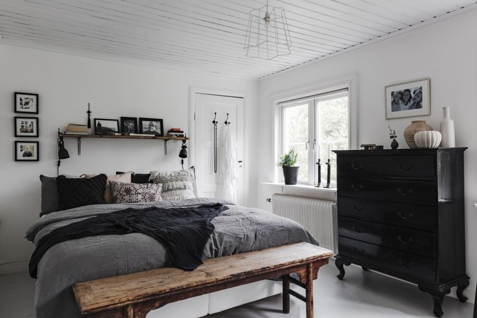 спальня кровать скамья окно белые стены светлый пол комод