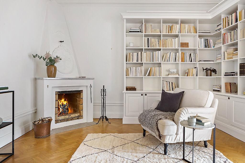 книжный шкаф кресло камин ковер