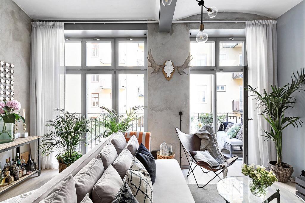 высокий потолок бетон серые стены французские двери окна диван подушки кресло