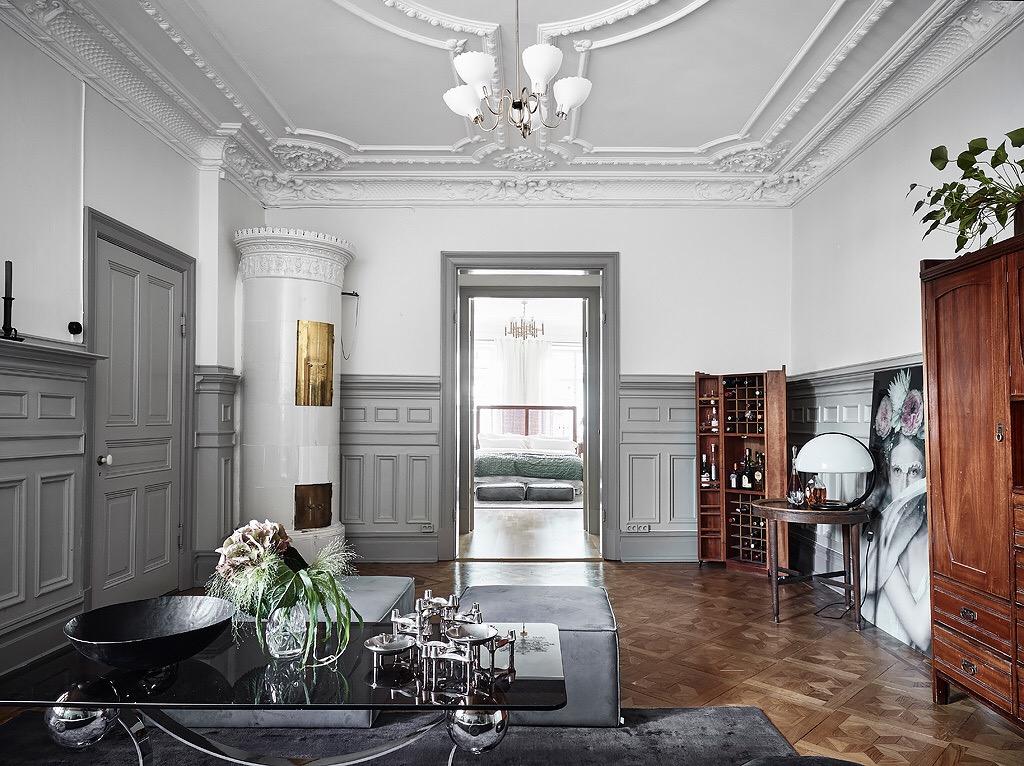 гостиная комната потолок лепнина скандинавская печь серые стеновые панели молдинги двери наличники винный шкаф паркет