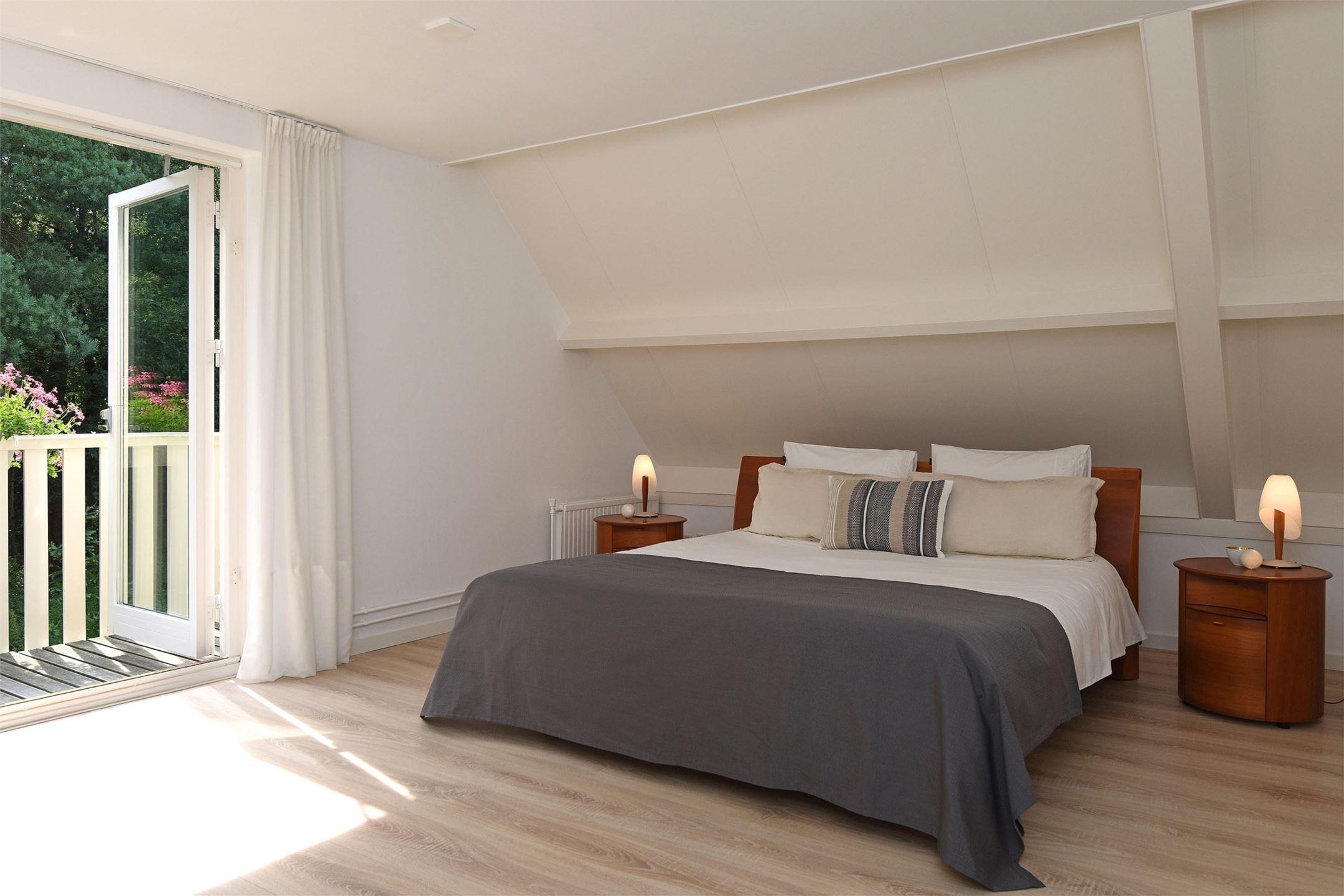 мансарда спальня кровать прикроватные тумбы лампы выход на балкон