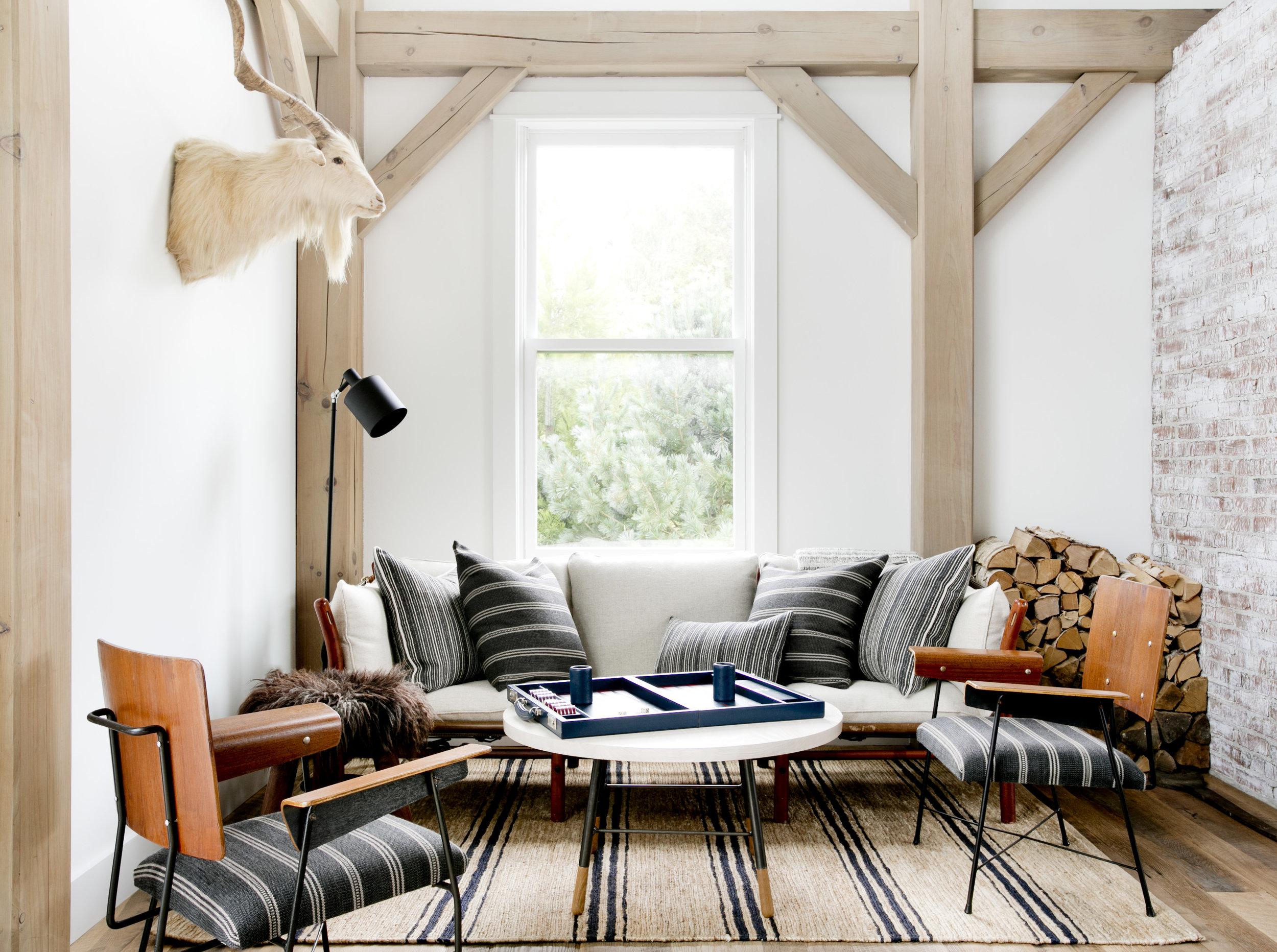 балки окно диван подушки дрова кресло круглый столик ковер деревянный пол