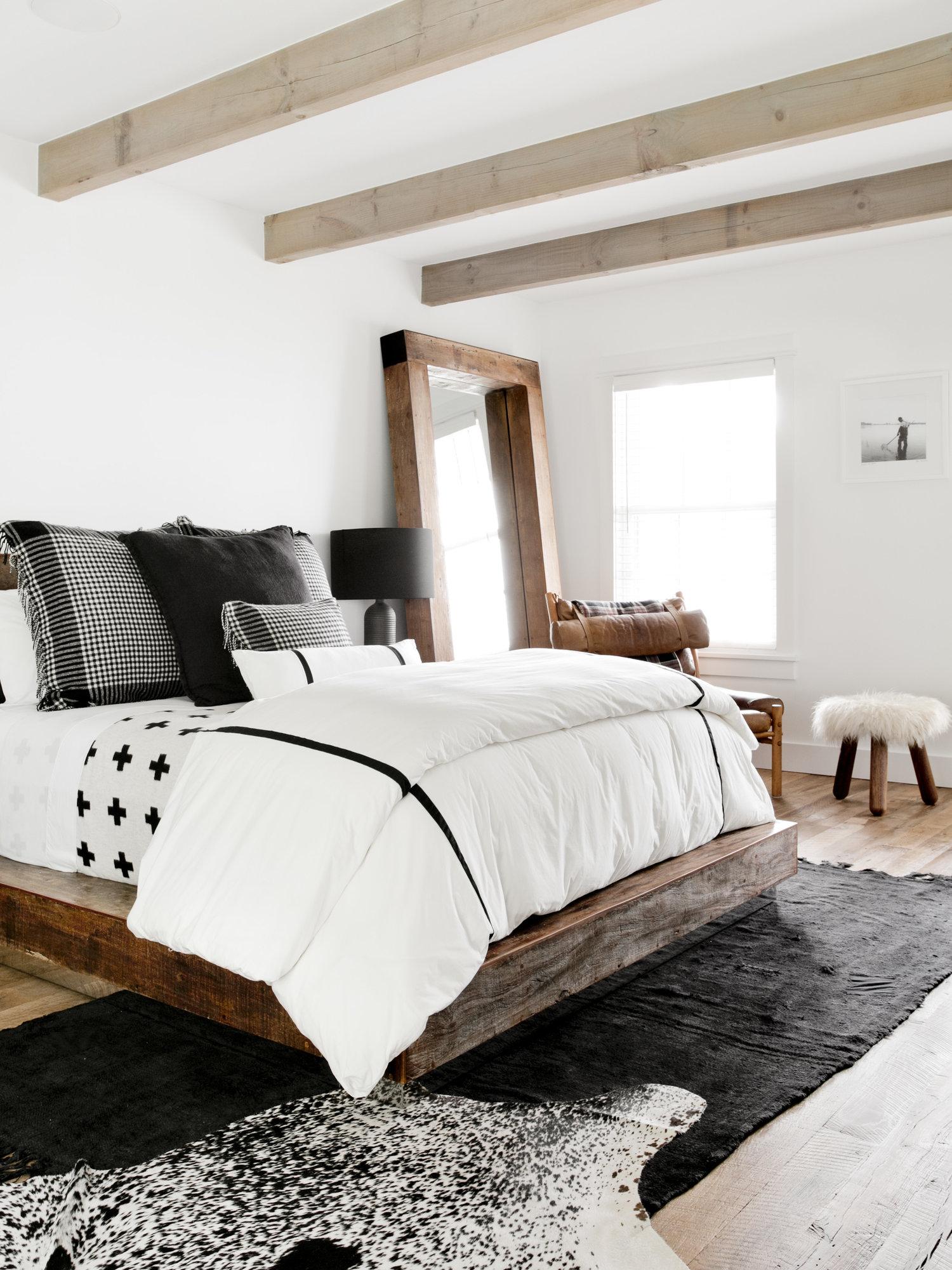 спальня потолок балки шкура кровать подушки текстиль напольное зеркало