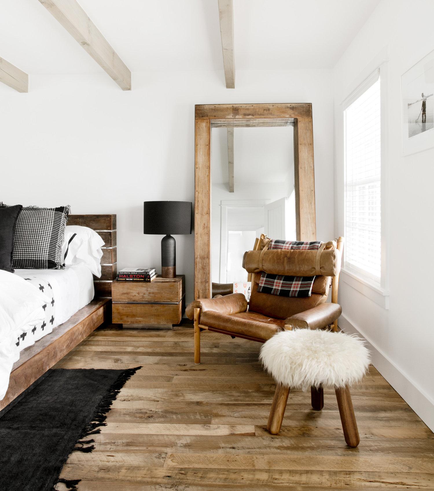 спальня белые стены деревянный пол потолок балки прикроватные тумбы лампы напольное зеркало кожаное кресло табурет