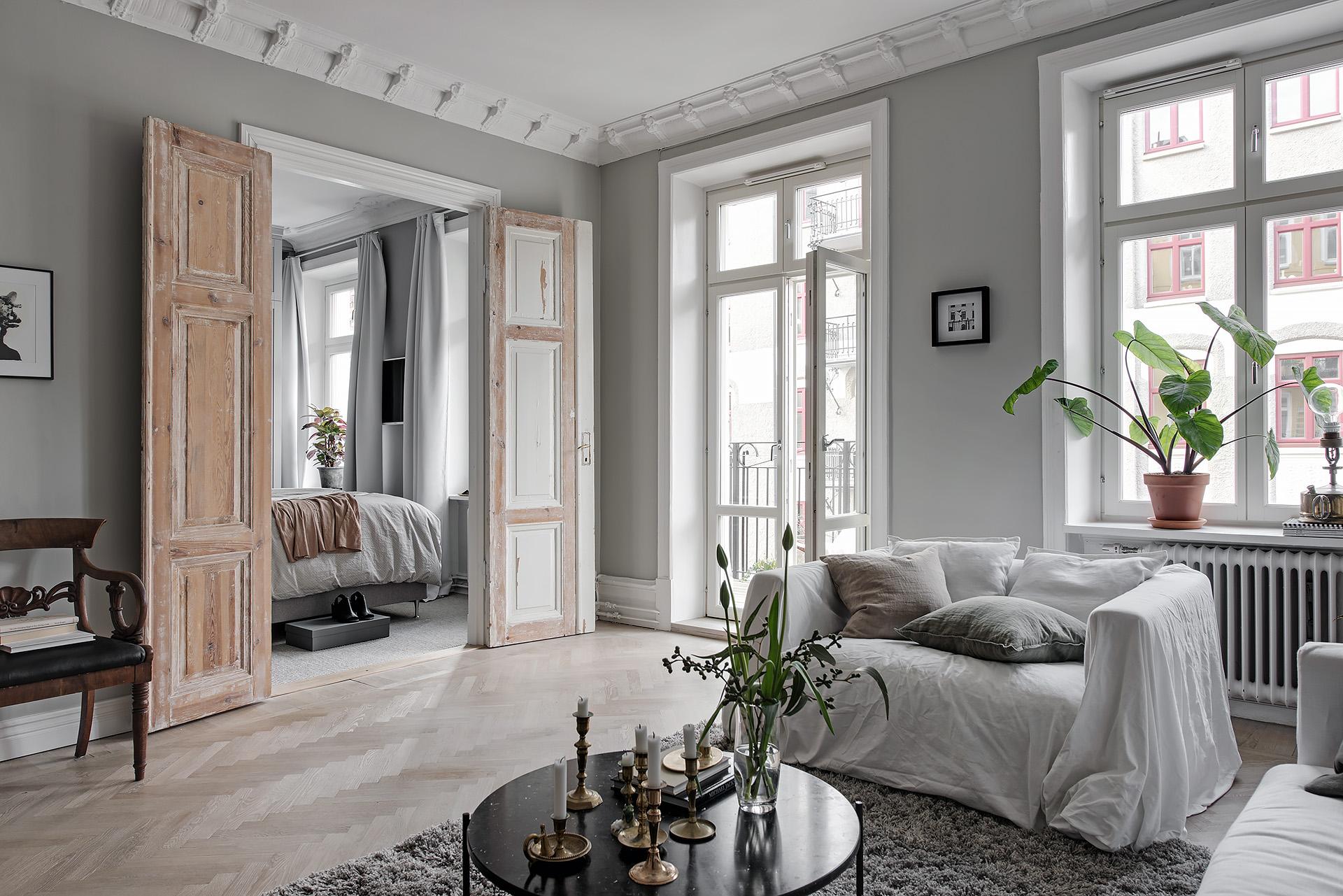 гостиная окно выход на балкон паркет елочка серые стены диван подушки круглый столик деревянные распашные двери
