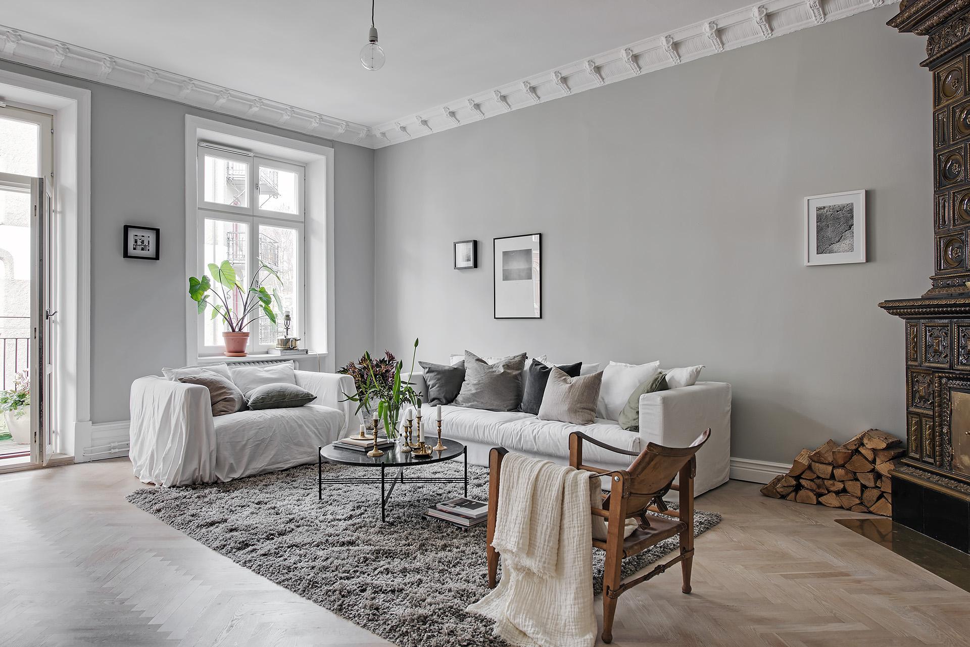 гостиная паркет елочка израсцовая печь дрова серые стены потолочный карниз лепнина белый диван подушки