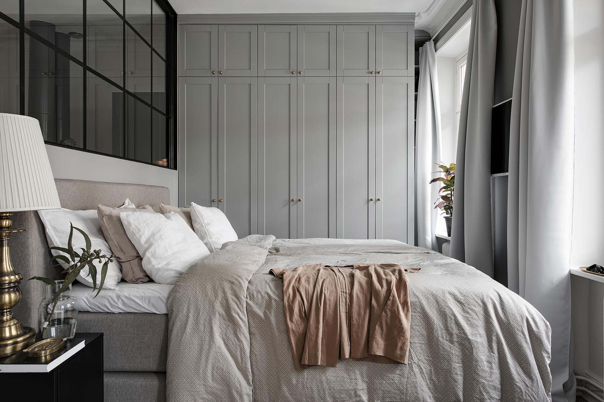 спальня кровать изголовье текстиль подушки прикроватные тумбы лампы окно шкаф телевизор