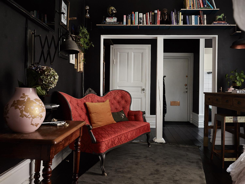 черные стены красный диван с утяжками темный пол наличники плинтус