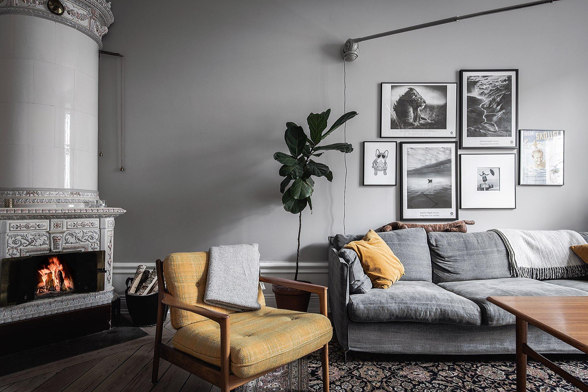 гостиная серые стены высокий белый плинтус картины серый диван желтое кресло израсцовая печь дрова