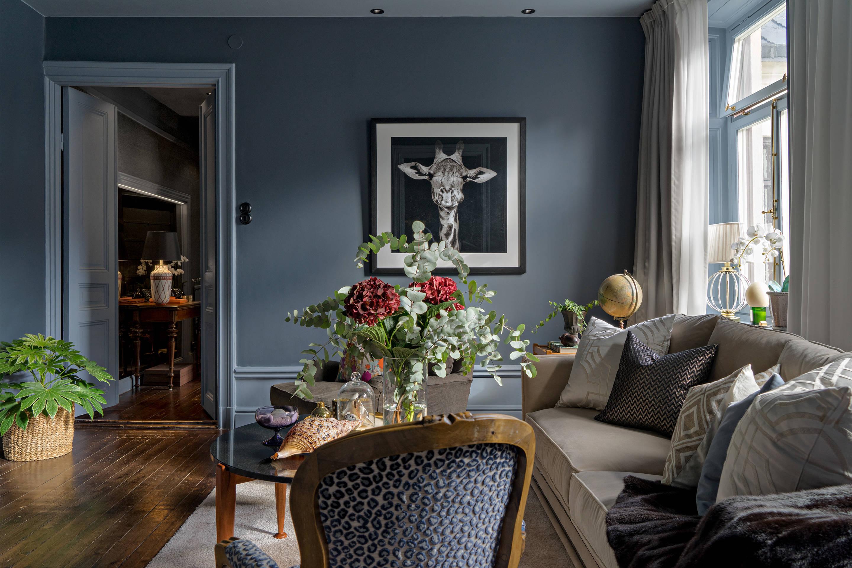 гостиная серые стены высокий плинтус дверь наличники бежевый диван подушки кресло деревянный пол