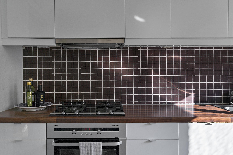 кухня белые гладкие фасады деревянная столешница газовая панель духовка встроенная вытяжка фартук мозаика