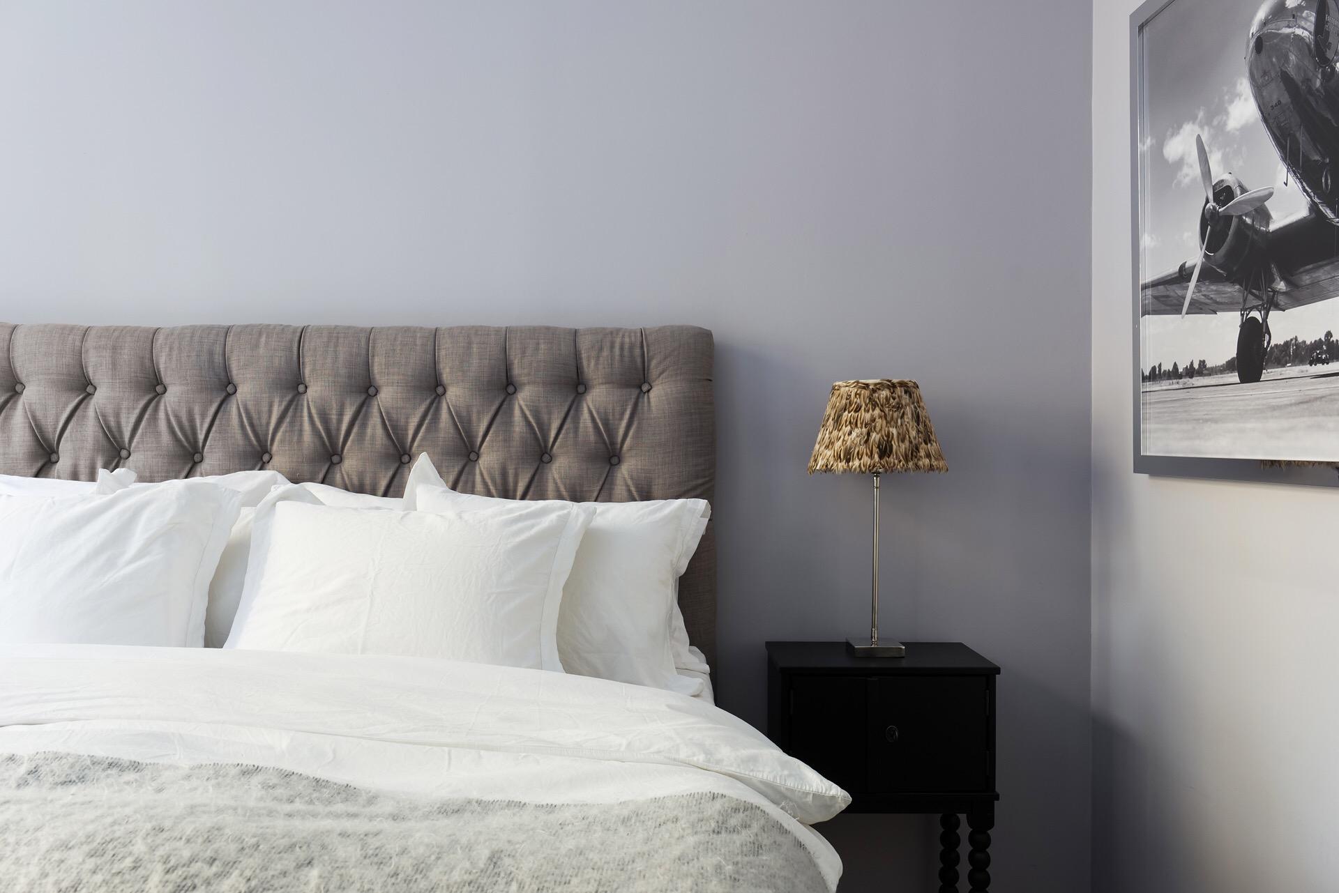 спальня кровать изголовье с утяжками подушки прикроватные тумбы лампы картина постер