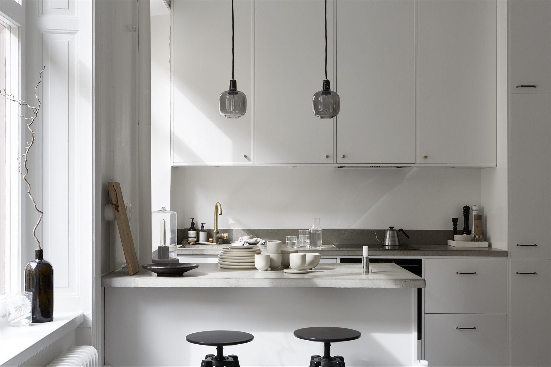 кухонная мебель белые фасады бетонная столешница остров барные стулья посуда