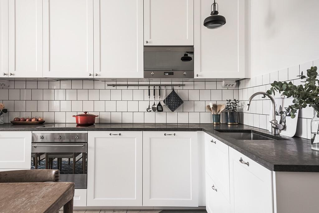 кухонная мебель белые фасады филёнка белая квадратная плитка деревянная столешница варочная панель духовка встроенная вытяжка мойка смеситель