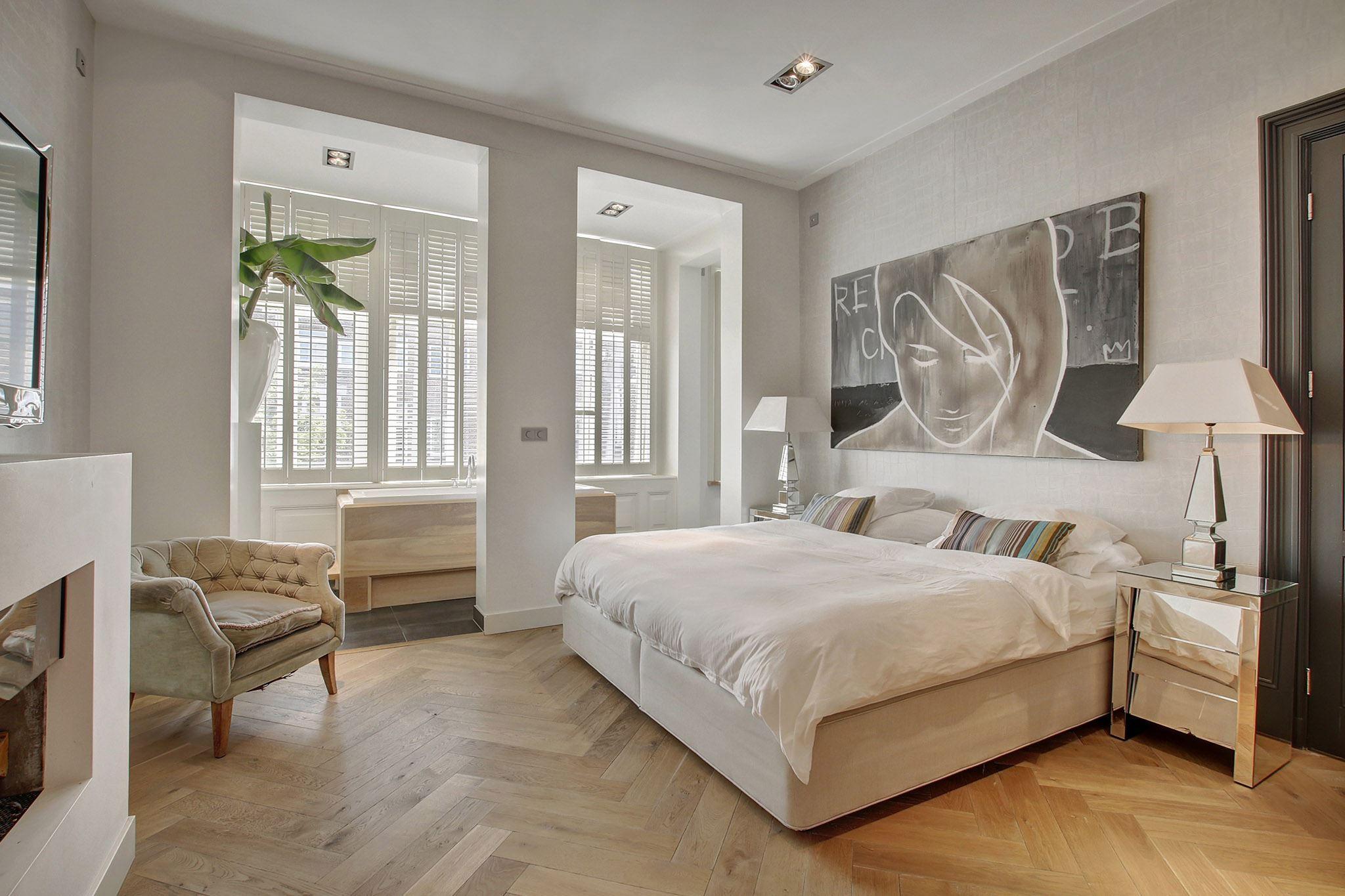 спальня колонны окно ванна кровать прикроватные тумбы лампы кресло камин телевизор паркет елочка