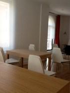 El aula visto desde el fondo. La pizarra camuflada en la pared , las cortinas rojas...