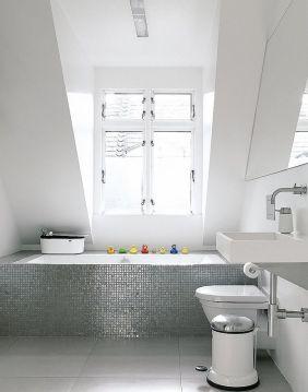 Un gresite plateado multiplica la luz que entra por la ventana, a la vez que añade interés a un espacio totalmente blanco brillante. Duravit y Corian son las firmas del sanitario y el lavabo respectivamente.
