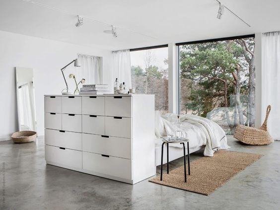 cama en el centro del dormitorio con mueble de ikea