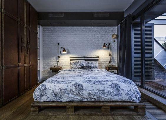 decoralinks | apartamento loft industrial - dormitorio con pared de ladrillo y base de la cama con pallets