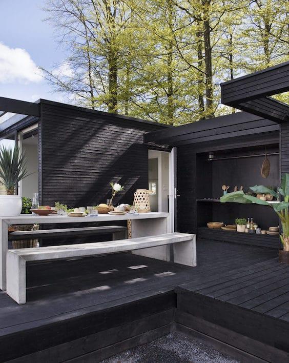 decoralinks | fachada de madera en color negro combinado con muebles de hormigon