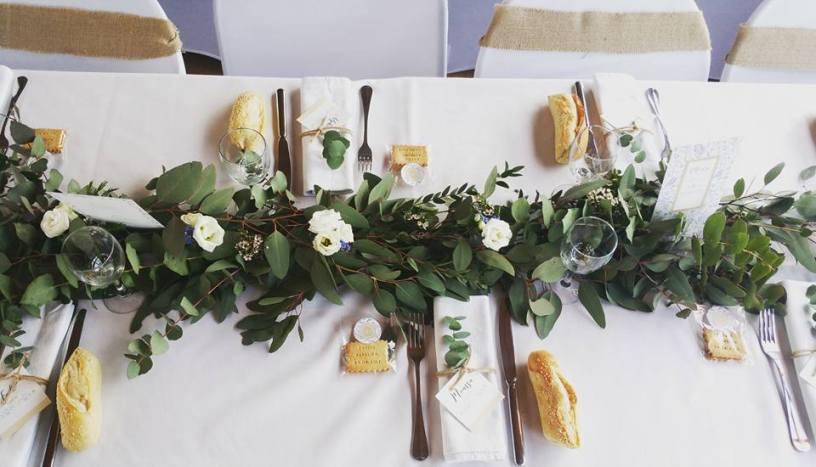 Décoration champêtre avec guirlande d'eucalyptus et incrustation de lisianthus, wax et myosothis.