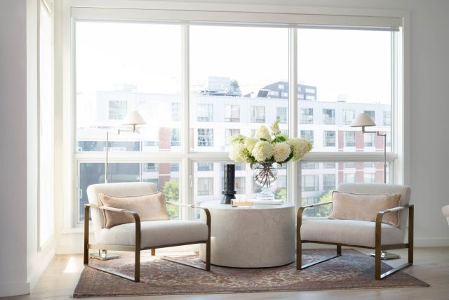 Two chairs and coffee table with a big window in the background