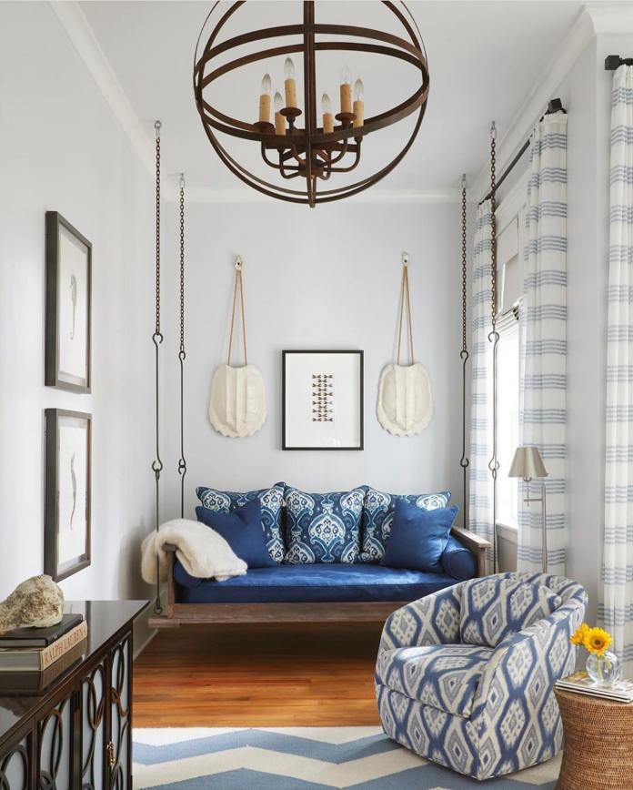 Living room with chair, couch with blue pillows and round chandelier