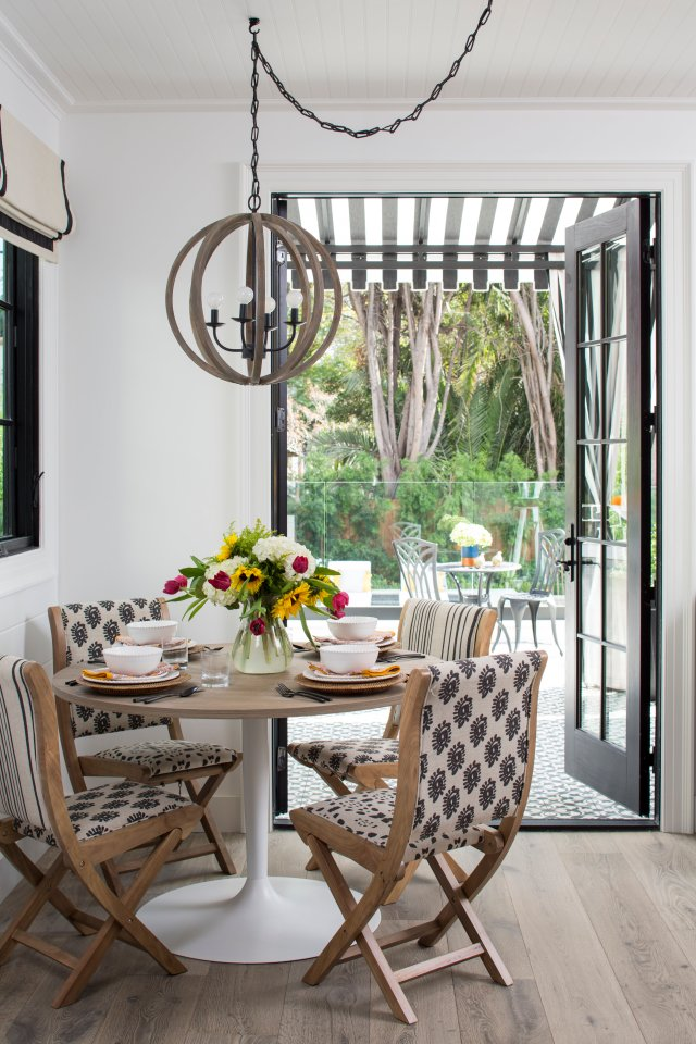 Table surrounded with chairs, sunflowers in a vase and big doors leading to yard