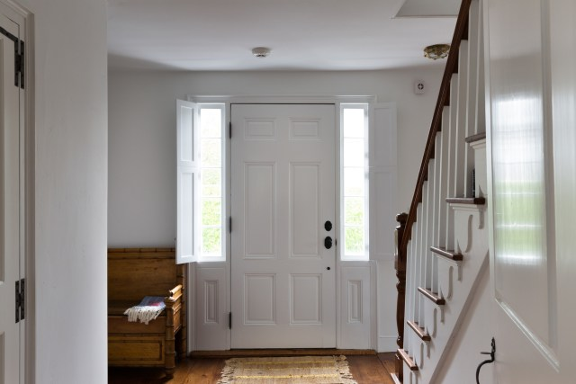 Hall looking to white entrance door