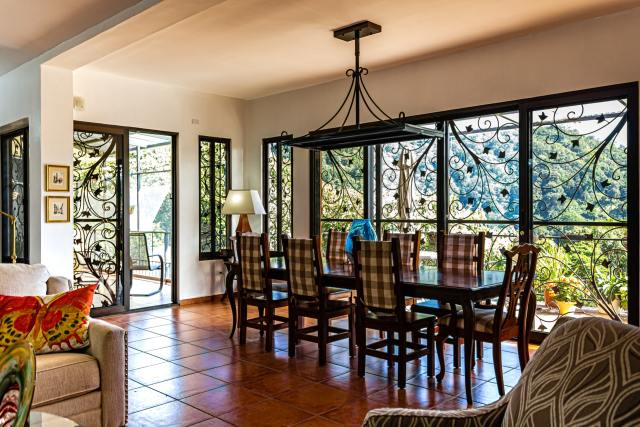 Decorated dining room with tile flooring, table and chairs and big windows
