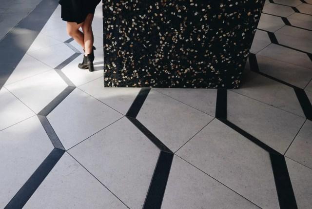 Tile flooring and woman standing next to pillar