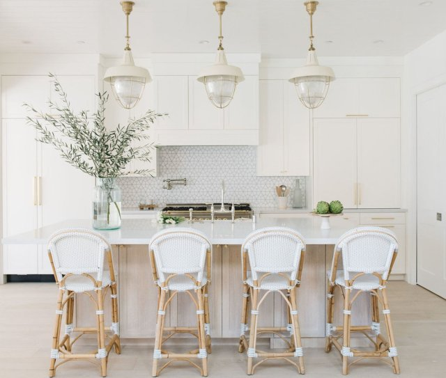 White designed kitchen with bar table and chairs, hanging lights and flowers in the vase on the table with kitchen elements in the background