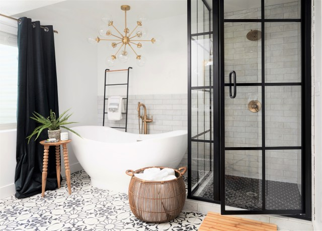 Bathtub and black shower with glass, black curtain and woven basket with laundry