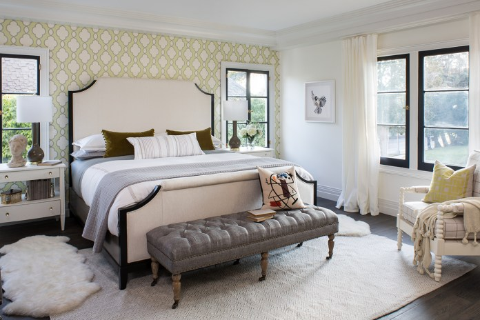 Beige bedroom with king bed and long chair in front of the bed