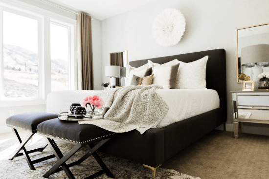 Bedroom with big white and black bed and chair with vase and flowers on it