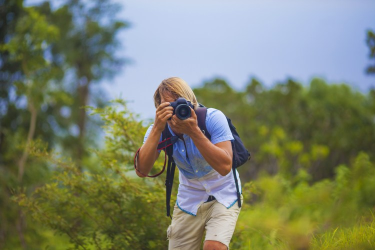 Photographer with Professional Digital Camera Taking Pictures in Nature