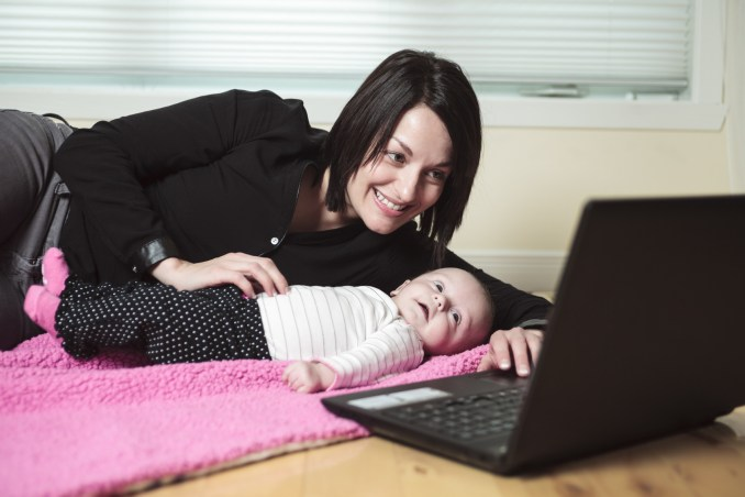 A mother with baby in font of a computer.
