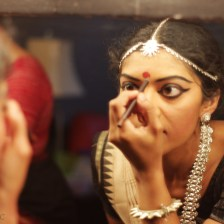 An odissi dancer drawing out precise makeup lines