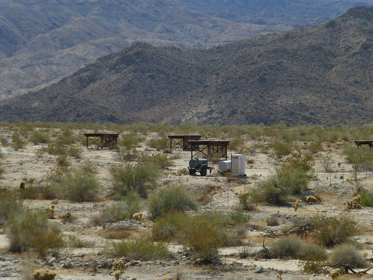 photo of a campground in creosote scrub desert, with some wooden shade structures.