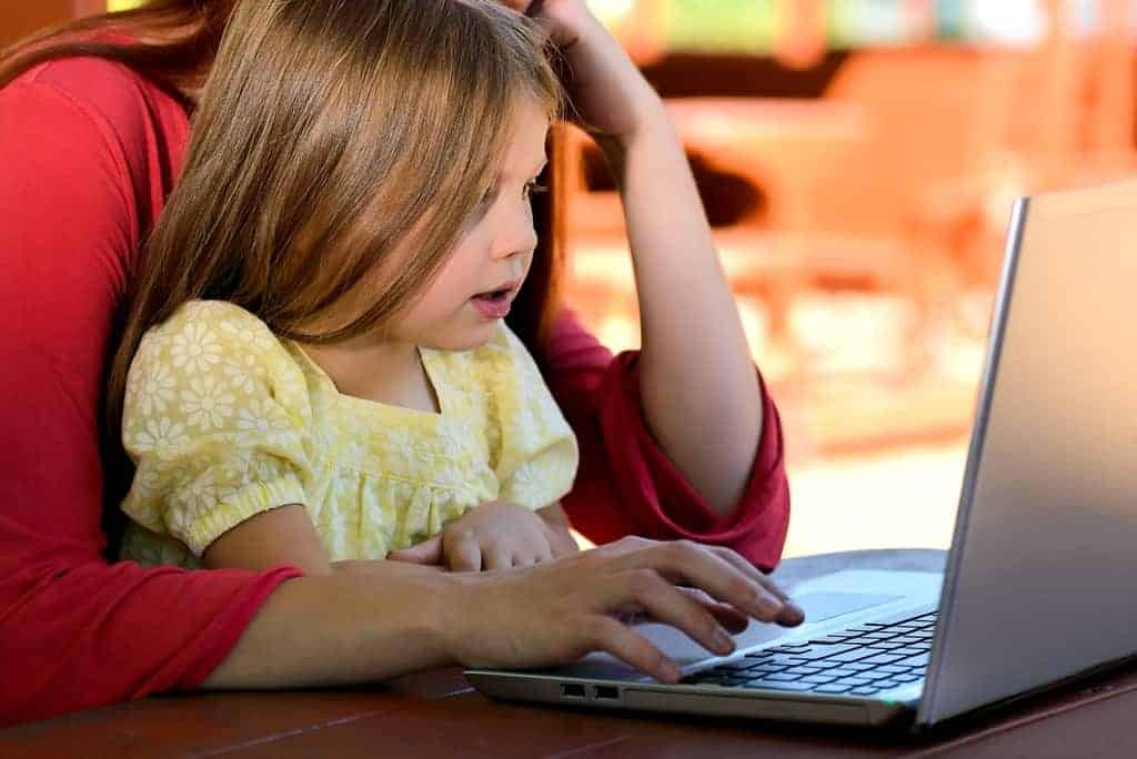 Little girl at computer with parent