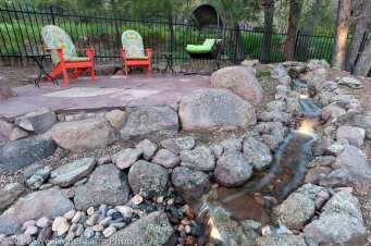 Locally harvested Chocolate Flagstone patio atop large site harvested boulders and rock work. Pondless water feature with falls accented by low voltage lighting.