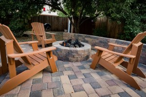 Paver patio and seat wall surrounding natural gas firepit