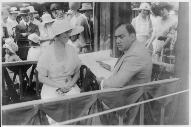 Caruso drawing caricature sketches in booth at a charity fair in Southampton, L.I., with Mrs. Albert Gallatin, August 3, 1920. Almost a year later to the day, on August 2, 1921, he died in Italy.