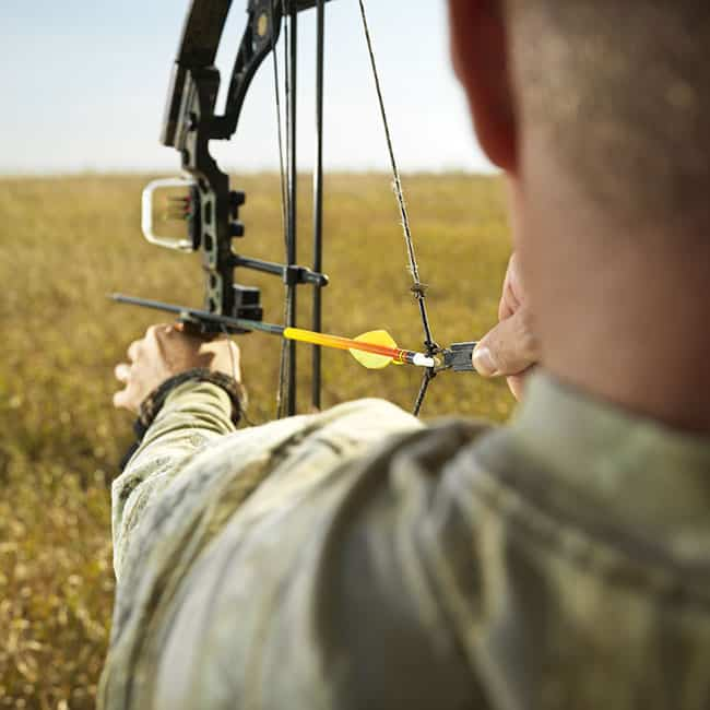 bigstock-Bow-hunter-in-field-pulling-ba-12817517 How to Measure Draw Length- Acquiring the Best Archery Skills