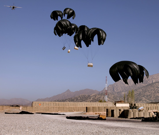 Bundles of bottled water attached to parachutes fall from an aircraft during an aerial resupply on Combat Outpost Herrera, Paktiya province, Afghanistan. Photo:  Staff Sgt. Andrew Smith