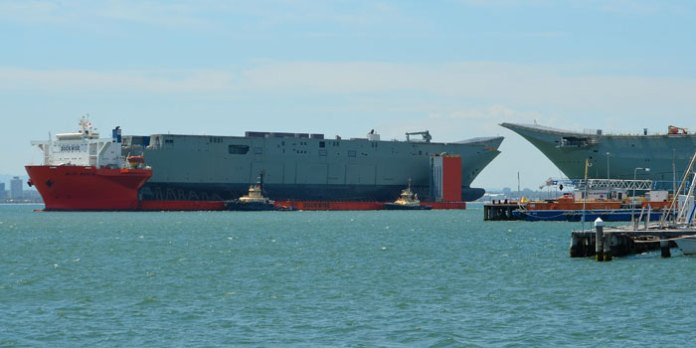 The new hull of Nuship Adelaide carried by the Blue marlin passes by Nuship Canberra nearing completion at BAE Melbourne. The Adelaide was ferried from Spain to Australia. Photo: Ross Johnson
