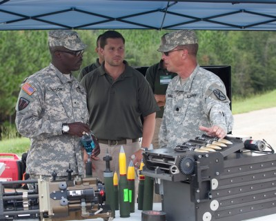 Brigadier General Lester Simpson receives a briefing from Col. about the new cannon's feeding system.