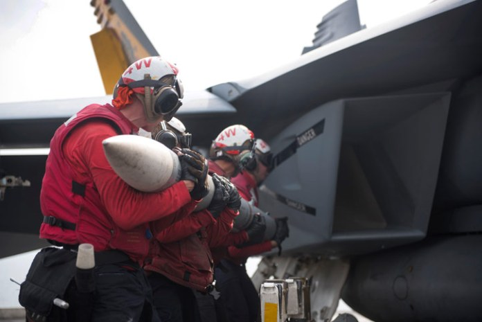 Aviation Ordnancemen assigned to Strike Fighter Squadron (VFA) 25, upload an AIM-120 AMRAAM missile to an F/A-18E Super Hornet on the flight deck of aircraft carrier USS Harry S. Truman (CVN 75). Photo: US Navy by E. T. Miller